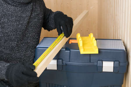 a man in black gloves measures the size of a wooden block on a tool box