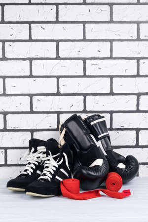 shoes and boxing gloves, red protective bandages for protecting hands on a white brick background