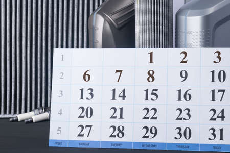 calendar of car maintenance, against the background of various spare parts