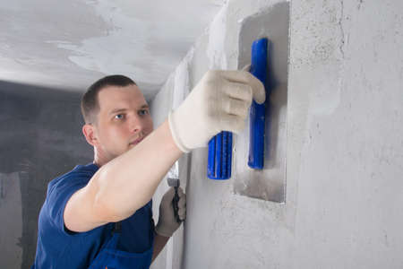 repair master of concrete walls, plasters the joint of the wall with the ceiling, close-up