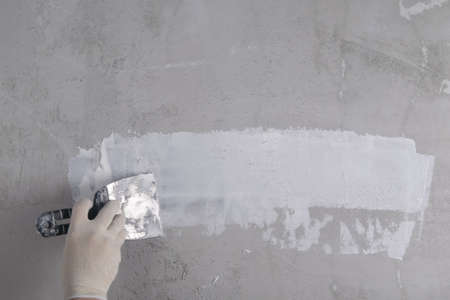 applying the finishing putty on a concrete wall, by the hand of a master, there is a place for the inscription Standard-Bild