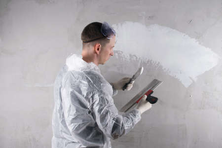the master works on leveling the concrete wall, a large spatula, applies a white solution, there is a place for the inscription