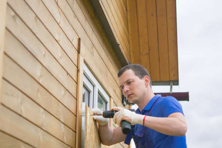 worker, blocks the window of the house with a protective shield made of wood, from thieves, when moving to another address