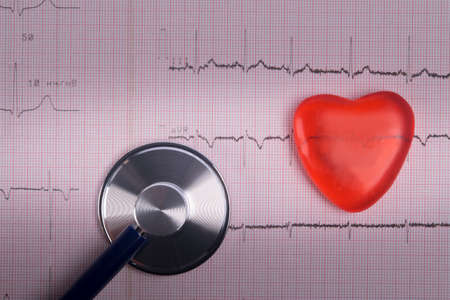 on the background of a cardiogram, with dimming, phonoscope and the image of a red heart, close-up