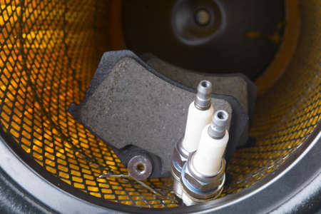 brake shoes of a car and two spark plugs for maintenance, against the background of a bright orange air filter