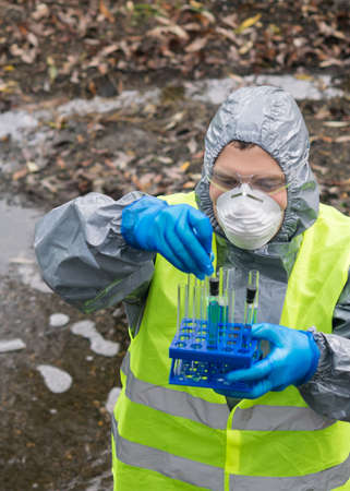 a man in a protective suit holds a stand with test tubes in which reagents and test materials against the background of the river, front view