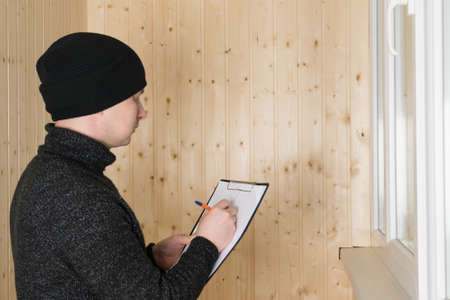 a man in warm clothes and a hat writes down the results of the work on warming the loggia Standard-Bild