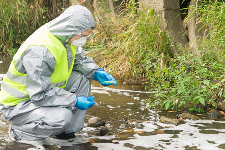 a man in a protective suit holds a Petri dish with a sample for plants and looks at the reaction in it after adding the reagent, side view against the background of the river