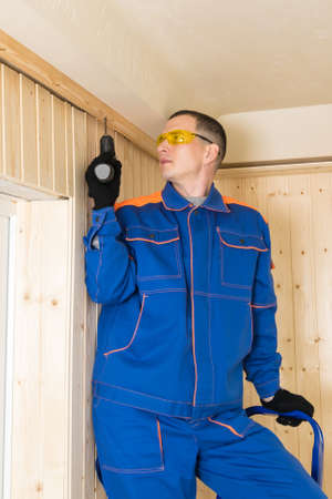master in blue special clothes screw the beam for boards with a screwdriver