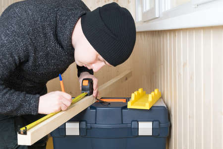 a man in black gloves measures the size of a wooden block on a tool box and takes notes Standard-Bild