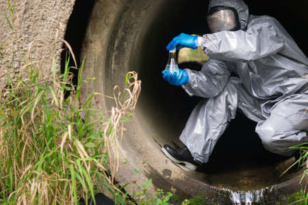 a man in a protective suit and mask in a large sewer took a sample of water for analysis