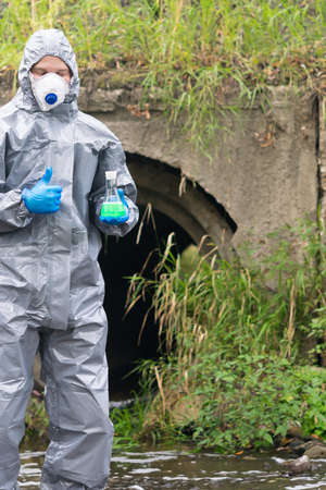 a man in a protective suit and mask holds a flask of green liquid in his hands and shows his thumb up on the background of sewage pipes coming out from the factory