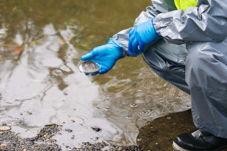 a man in a protective suit and mask took a soil sample from the bottom of the river into a Petri dish, close-up