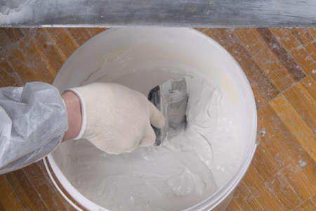 close-up of a bucket, with finishing putty for concrete walls