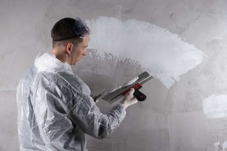 a man with a spatula repairs a wall with plaster
