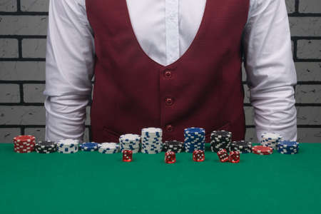 poker chips are stacked on a green cloth in front of them are red dice, in the background is a croupier in a vest