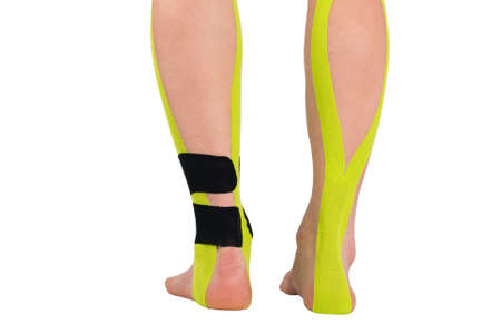 injured lower part of two legs with pain relief tape glued on, isolated on white, back view 版權商用圖片