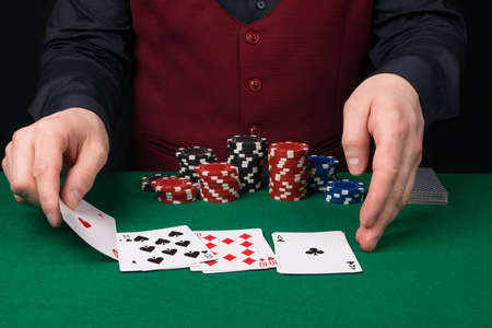 the croupier at the green table removes the playing cards for poker