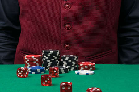 there are black and red chips on the green table, next to red dice, the croupier's background Stockfoto