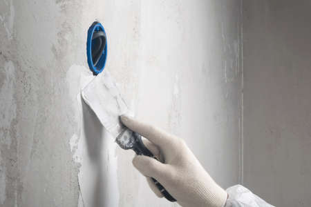 the hand of the master in a glove with a spatula covers the wall with mortar after laying the electrical wires for the outlet, repair