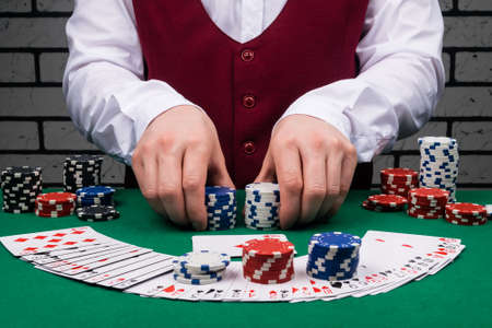 the dealer's hands are holding stacks of poker chips and cards and chips are on the green cloth