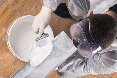a worker in a protective suit and goggles applies the finishing putty for the walls on the spatula, repair, top view