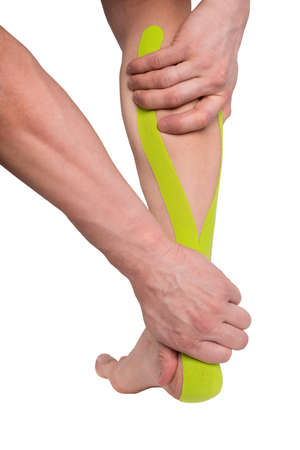 hands holding injured lower part of the leg with medical tape applied to relieve pain, isolated on white 版權商用圖片