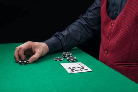 a croupier in a black shirt and vest holds chips in his hands, and on the green table lies a winning five-card poker hand, side view Stockfoto