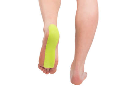 medical tape glued to the sole of the foot to reduce pain from injury and for treatment, isolated on white, back view