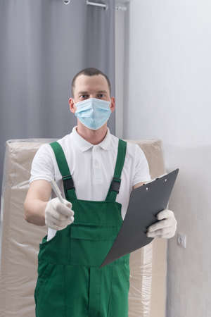 deliveryman in a protective mask and gloves, gives to sign documents, before handing over the parcel