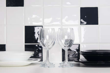 on a white-black tile background, on the table there are clean dishes, plates and glasses