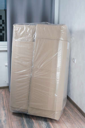 delivered a large cardboard box in protective plastic to the apartment