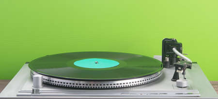 against the background of a green wall, with a place for an inscription, an old turntable Stockfoto