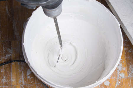 mixing wall putty with a whisk in a bucket, for finishing application