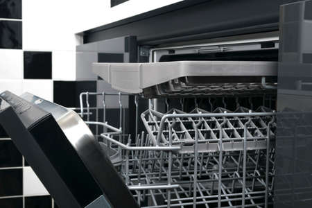 close-up of a dishwasher without dishes, on the background of black and white kitchen tiles Stockfoto