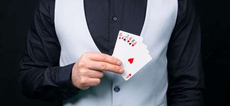a combination of cards of a large win in hand, against the background of black clothes of the croupier