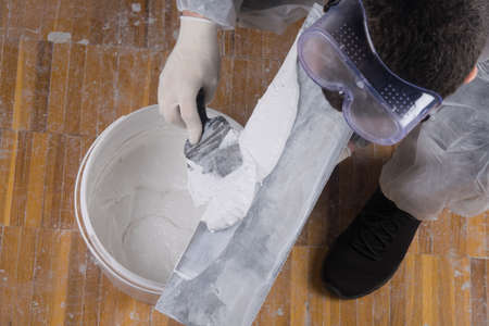 on a large spatula, apply a mixture for sealing cracks from a bucket, top view