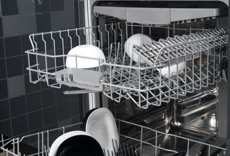 Close-up of dishwasher drawers, with black and white plates Stockfoto