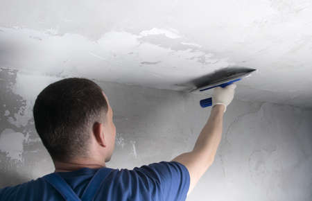 master in a blue uniform, applying the finishing putty on the ceiling, close-up