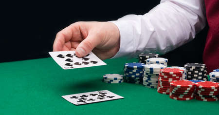 close-up of a croupier's hand with playing cards, against a background of green cloth and poker chips Stockfoto