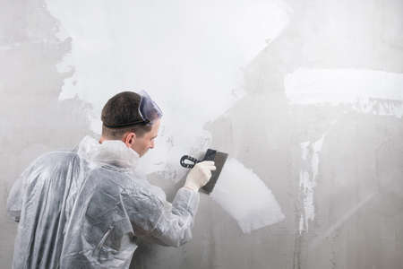 a repairman applies the mixture to the wall to level it
