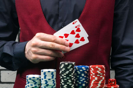 a croupier in a black shirt and a red yolk holds cards of black and red suits in front of chips for playing poker