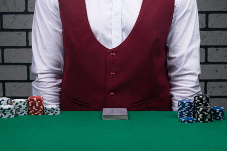 on the green cloth of the table lies a deck of poker playing cards in front of the dealer