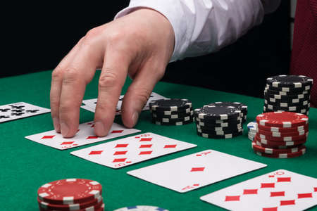the dealer's hand opens the cards on the green cloth of the poker table, side view