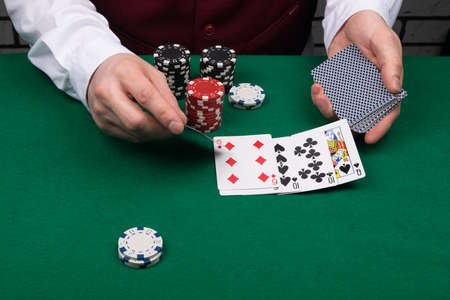 the croupier closes the winning combination on the green cloth of the poker table, close-up view Stockfoto