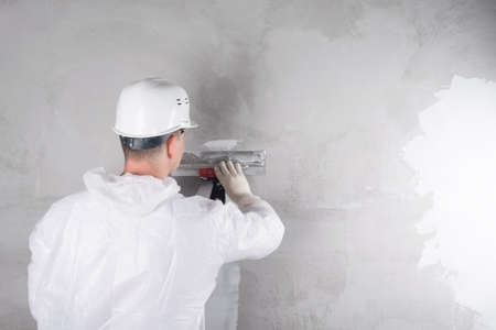 a worker in a helmet and a suit applies the mixture to the wall to level it, rear view