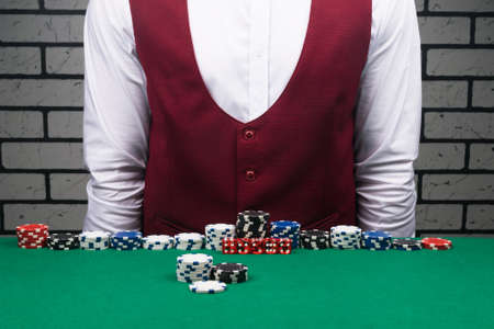 the croupier stands at a table with poker chips