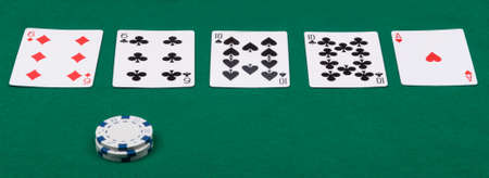 a combination of poker cards and chips is laid out on a green cloth