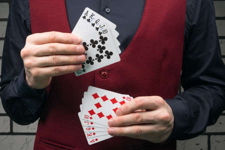 the croupier in a black shirt and red vest holds cards of black and red suit
