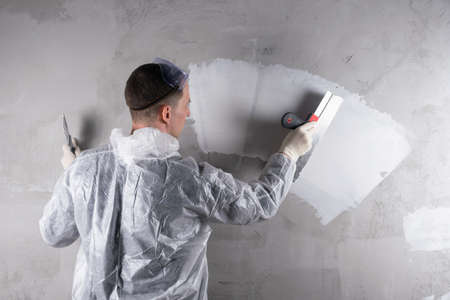 master plasterer makes a white strip with a trowel on a concrete wall, place for your lettering Stockfoto